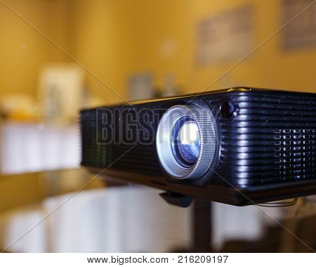 Modern technology, a black projector on the glass table prepared to broadcast video and presentations on a large screen in the audience. Organization and conduct of training events.