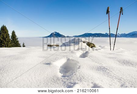 Pair of red ski sticks and footsprints in snow. Sporting activity in mountains winter landscape. Allgau Alps, Bavaria in Germany.