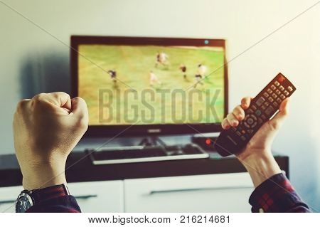 Goal. Man watching football match on television at home. remote control in hand. football fan watches world Cup soccer and more for your favorite football team
