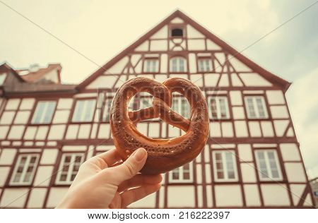 Pretzel in hand of tourist in Germany. Bavarian house of historical city and traditional piquant or sweet pastry.