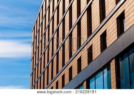 Brick facade of modern urban building on the background of sky in sunny day, Saint Petersburg, Russia