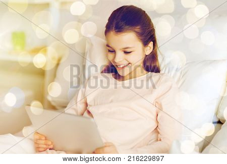 people, children and technology concept - happy smiling girl lying awake with tablet pc computer in bed at home over holidays lights background