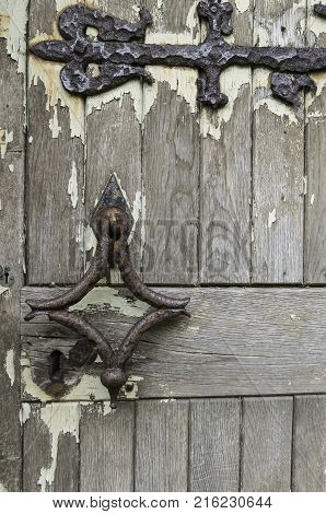 The door of a derelict medieval church with signs of extreme weathering
