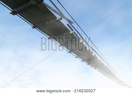 view from below on an old wooden suspension bridge against a sky hiding in clouds in perspective
