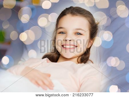 people, children, rest and comfort concept - happy smiling girl lying awake in bed over holidays lights background