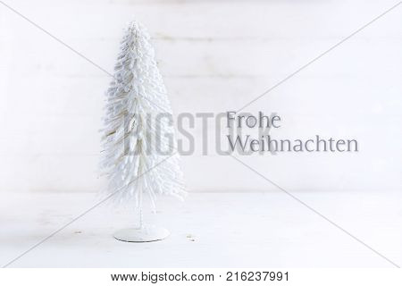 white christmas tree made of flocked wire on rustic white painted wood with german text Frohe Weihnachten meaning Merry Cristmas greeting card