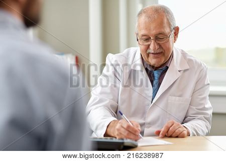 medicine, healthcare and people concept - senior doctor writing prescription for young male patient at hospital