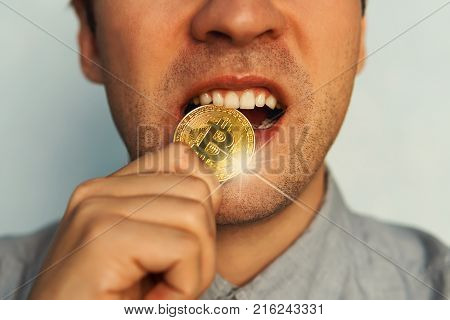 man with one gold bitcoin coin on a tooth. Test of strength gold coin bitcoin.