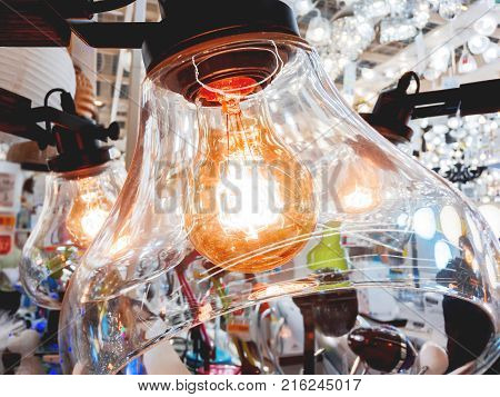 Chandelier with transparent glass plafonds and old fashioned light bulbs. Vintage light bulbs with glower filament. Incandescent retro design.