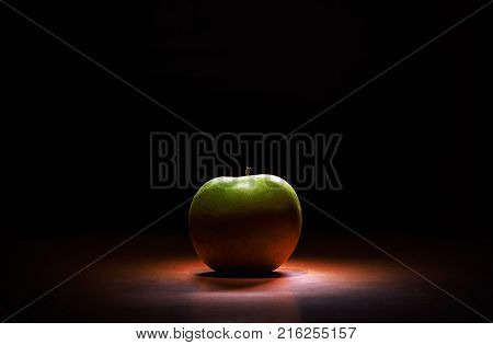 Studio shot of fresh green apple accentuated shapes with illumination.