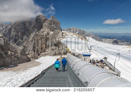 DACHSTEIN MOUNTAINS, AUSTRIA - JULY 17, 2017: People going down at stairs to surface of Dachstein glacier surrounded with bare mountain peaks covered with clouds