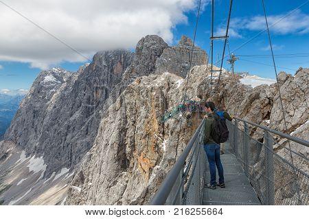 DACHSTEIN MOUNTAINS, AUSTRIA - JULY 17, 2017: Dachstein Mountain in Austria with hikers passing a steel skywalk rope bridge