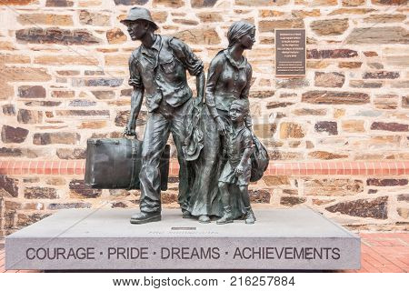 Adelaide SA Australia - November 20 2009: Black bronze statue of migrants show husband and wife with one child all packed with luggage looking around celebrating courage pride dreams and achievements.