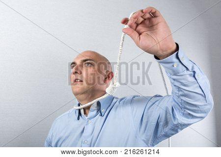 Depressed man plans his suicide with a rope, portrait
