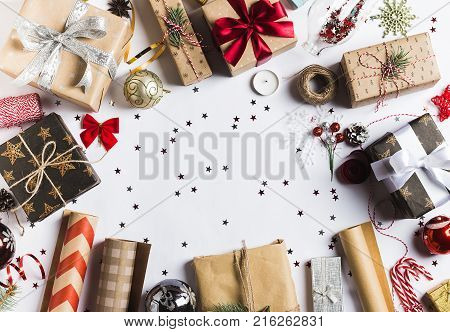 Package christmas gift box. New year christmas packaging wrapping paper ribbon twine bow and thread christmas balls on white background. Winter time new year poster