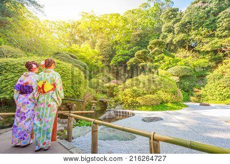 Kamakura, Japan - April 23, 2017: two women wearing in traditional japanese kimono looking japanese zen garden inside Take-dera Temple in Kamakura. Sunset light. Meditative and buddhism concept