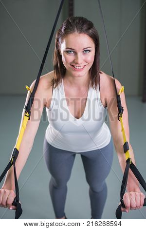 Young woman doing suspension training push-ups with fitness straps