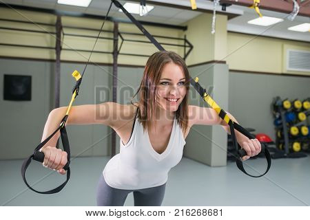Young happy woman bodybuilder at gym doing elastic rope exercises with with suspension fitness straps