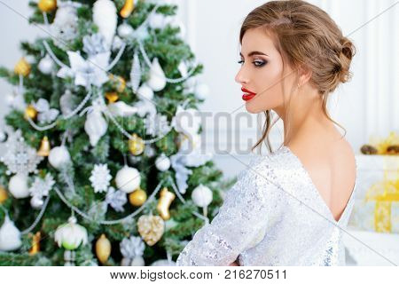 Portrait of a beautiful young woman with evening makeup and hairstyle poses near the Christmas tree. Holiday make-up and hairstyle. Beauty, fashion. Merry Christmas and Happy New Year.