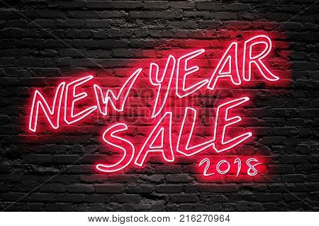 NEW YEAR SALE 2018 concept. text fluorescent Neon tube Sign on dark brick wall. Front view. Can be used for online banner ads or background. night moment.