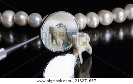bad rotten tooth pulled and stands opposite the offices of the mirrors and dazzling white pearls on a black isolated background