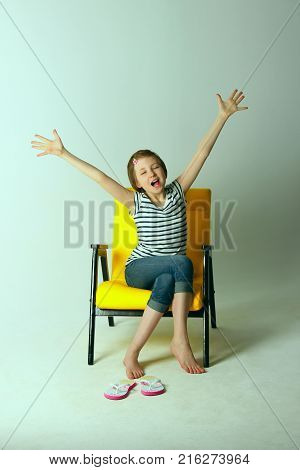 Yellow Arm Chair and Holding Hands Up.Tired sleepy girl yawning. Shot of a young girl stretching her arms and yawning.