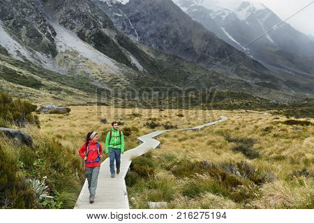 New Zealand trampers backpacking on Mount Cook / Aoraki Hooker valley travel. hikers hiking walking on Hooker Valley Track in summer on boardwalk. Couple on travel holiday adventure.
