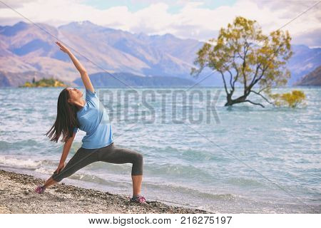 Yoga wellness woman at Wanaka lake by the lone tree, New Zealand travel. Meditation yogi girl doing the exalted warrior pose in morning fitness exercise at the beach.