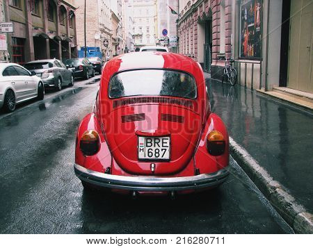 Budapest, Hungary - September 20, 2017: Back view of a red retro car on an ancient street in Budapest.