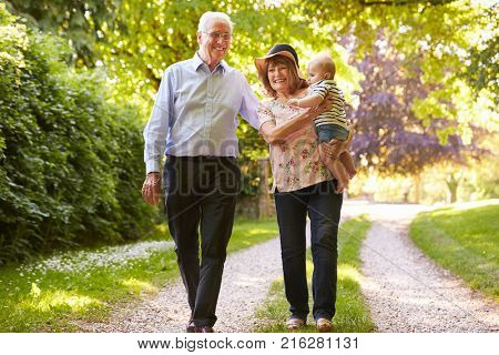 Grandparents On Walk In Countryside With Baby Grandson