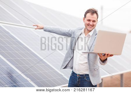 An employee of the solar station holds an open modern laptop, communicating through video communication, and showing a hand on the solar panel. Outdoors .