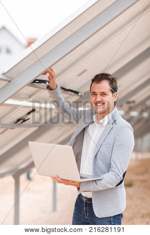 A young man holds an open modern laptop in his hands, and holds his hand behind the solar panel and smiles. Outdoors .