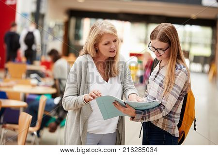 Teacher Talks To Student In Communal Area Of College Campus