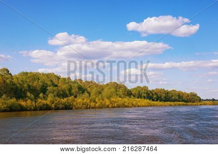 Calm landscape with river blue sky and white clouds. Bank of Oka River (Volga tributary) in Ryazan region. Russia