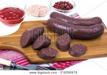 Homemade blood sausage with tomato sauce on wooden board. Studio Photo