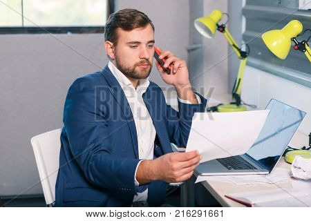 Young businessman in suit, sitting in office at desk, talking on mobile phone and examining documents. Indoors.