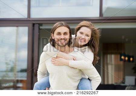 Young man holding woman on his back, husband piggybacking smiling wife standing outside modern own new house, happy loving couple having fun looking at camera, portrait, mortgage loan, real estate
