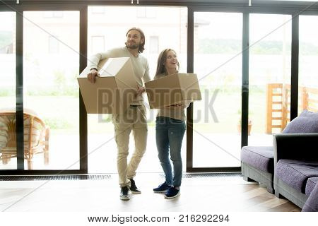 Happy young couple carrying cardboard boxes entering modern own house, excited married family property owners man and woman moving in into new home, buying real estate, mortgage and relocation