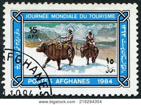 AFGHANISTAN - CIRCA 1984: A stamp printed in the Afghanistan devoted to World Tourism Day. Depicts Buffalo riders in snow, circa 1984