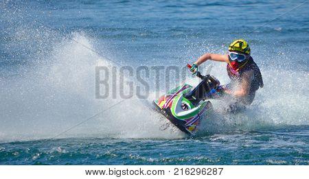 Jet Ski competitor cornering at speed creating at lot of spray.
