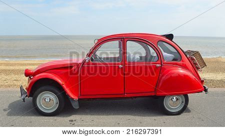 FELIXSTOWE, SUFFOLK, ENGLAND -  MAY 07, 2017: Classic Red Citroen 2CV  deux chevaux parked on seafront promenade.