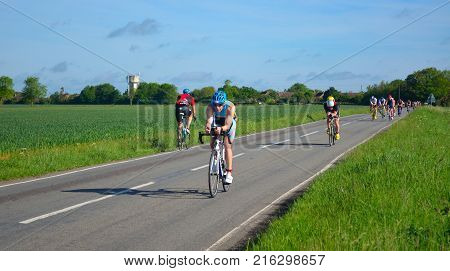 GRAFHAM, CAMBRIDGESHIRE, ENGLAND - MAY 22, 2016:  Triathletes on road cycling stage of triathlon riding in both directions.