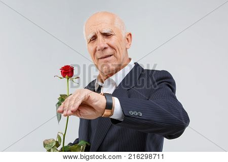 A handsome mature man in a black suit, looks at his wristwatch and durts in his hand one red rose. Isolation.