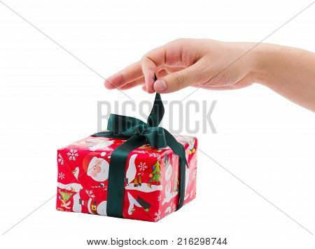 The man's hand of a European man unleashes a dark green bow of a Christmas gift box. Isolated on white background.