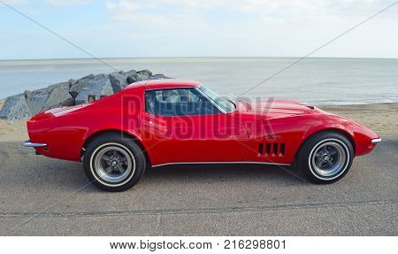 FELIXSTOWE, SUFFOLK, ENGLAND -  MAY 07, 2017: Classic Red Chevrolet Corvette Stingray  Motor Car Parked on Seafront Promenade.