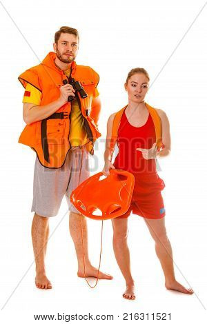 Lifeguards with rescue tube buoy and life vest jacket looking through binoculars. Man and woman supervising swimming pool. Accident prevention.