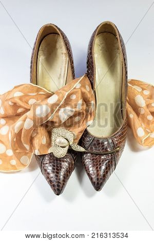 Composition with vintage women's snakeskin shoes polka dot scarf and rhinestone calla lily brooch on white vertical aspect
