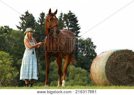 Woman in blue dress stay beside her horse near hayroll