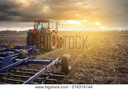 Tractor working on the farm, a modern agricultural transport, fertile land, tractor on a sunset background, cultivation of land, agricultural machine
