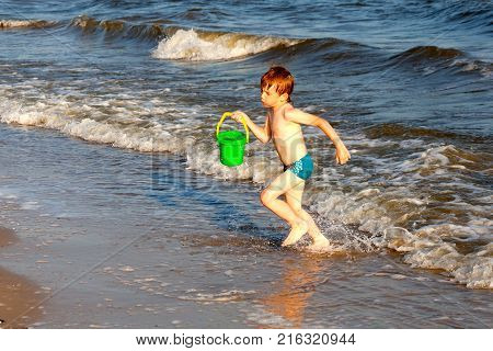 Happy boy having fun on the background of sea playing with buck and wate in sunset reys. Black sea in ukraine